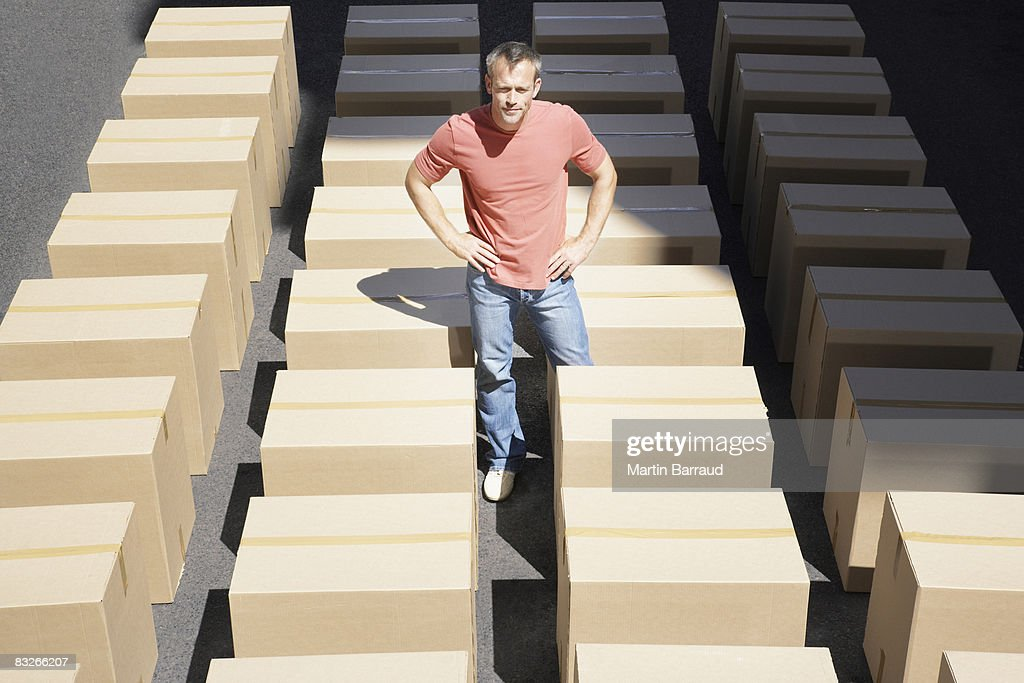 Man standing with lines of boxes in roadway : Stock Photo