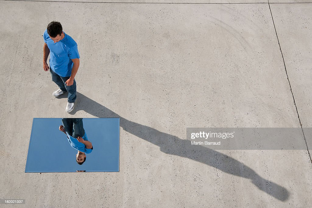 Man standing with mirror on ground and reflection : Stock Photo