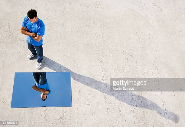 Man standing with mirror on ground and reflection