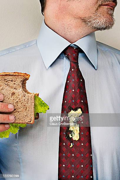 man standing with sandwicht and dressing on tie