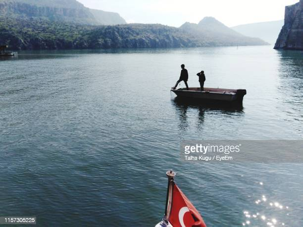 man standing with son in boat on lake - şanlıurfa stock pictures, royalty-free photos & images