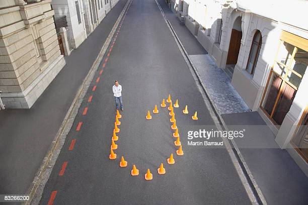 Man standing with traffic cones in shape of u-turn