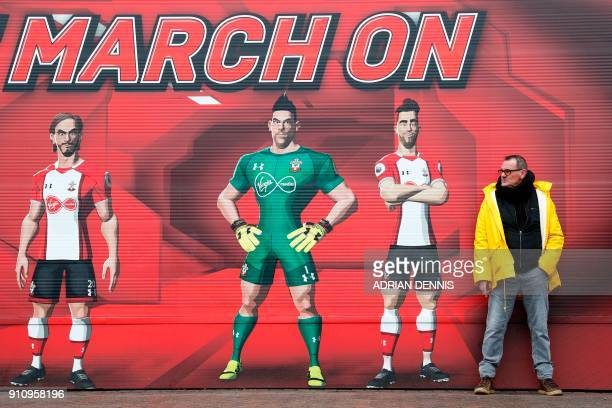 A man stands against a wall outside the stadium adorned with a message to 'March On' ahead of kick off of the English FA Cup fourth round football...