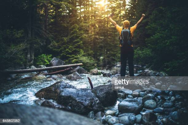 man stands alone at the edge of stream in mountains, his arms raised - pirin national park stock pictures, royalty-free photos & images