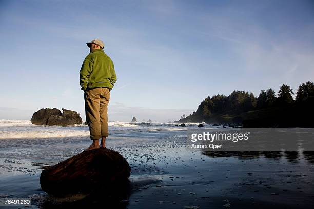 A man stands alone on a piece of wood on the beach near Redwood National Park.