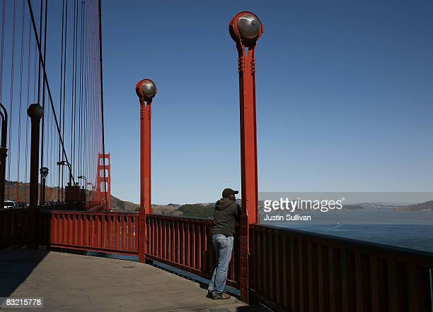 A man stands alone on the span of the Golden Gate Bridge October 10 2008 in San Francisco California The Golden Gate Bridge District board of...