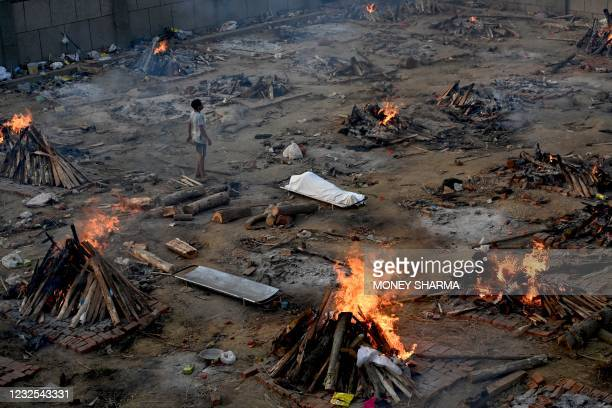 Man stands amid burning pyres of victims who lost their lives due to the Covid-19 coronavirus at a cremation ground in New Delhi on April 26, 2021.
