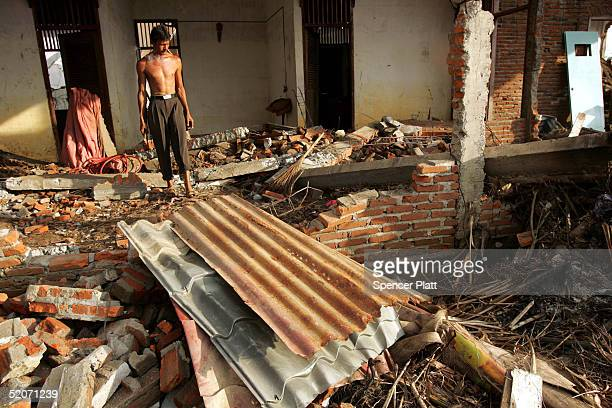 27 A man stands among the ruins of his home January 27 2005 in the tsunamiravaged town of Meulaboh Indonesia Over a month since the Indian Ocean...