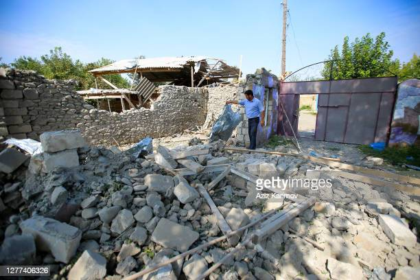 Man stands amongst rubble in a yard of a house which is said to have been damaged in recent shelling during clashes between Armenian separatists and...