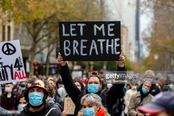 Man stands amongst thousands of protesters, all wearing facemasks, as he holds a large Let Me Breath placard during a Black Lives Mater rally on 06...