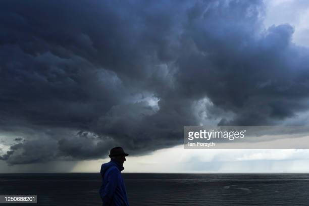 A man stands and looks as a storm cloud passes over the coast and out over the North Sea on June 19 2020 in Saltburn By The Sea United Kingdom