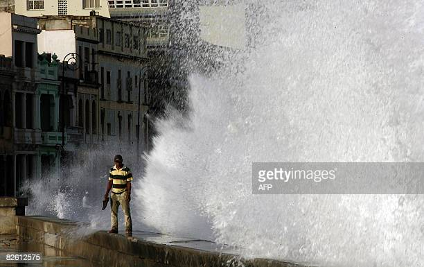 A man stands as a huge wave breaks in Havana's seafront on August 31 after the passage of Hurricane Gustav There were reports of dozens of injuries...