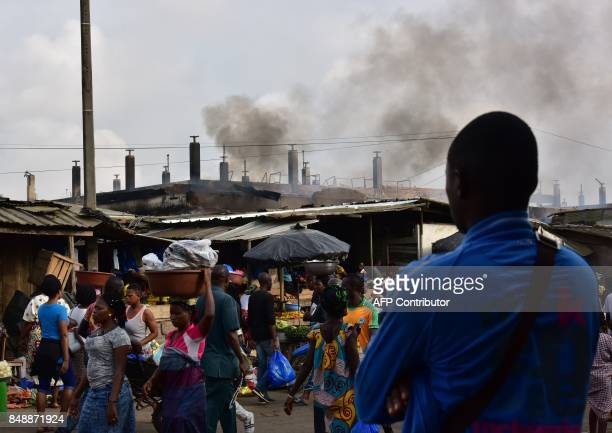 A man stands as people walk past the market after a fire devastated the building during the night on September 18 2017 in Abobo neighborhood of...