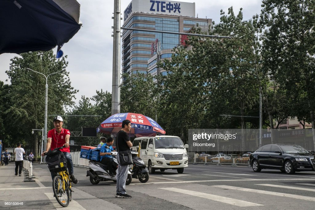 A man stands at a pedestrian crossing in front of a ZTE Corp. building in Beijing, China, on Thursday, May 24, 2018. PresidentDonald Trumpsaid the U.S. would allow Chinese telecommunications-equipment maker ZTE Corp. to remain in business after paying a $1.3 billion fine, changing its management and board and providing 'high-level security guarantees.' Photographer: Gilles Sabrie/Bloomberg via Getty Images