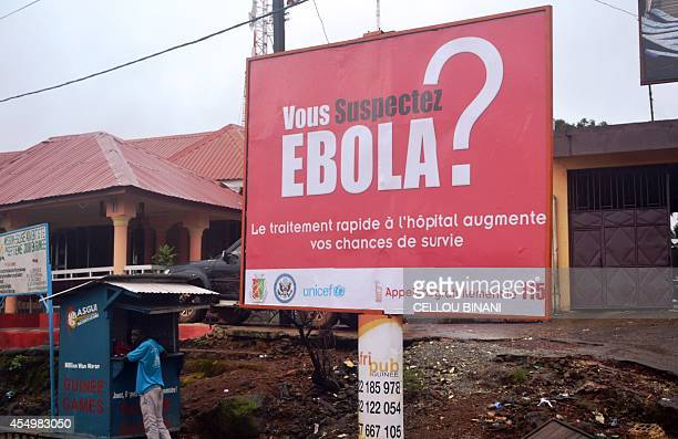 A man stands at a stall on September 8 2014 next to a billboard about the Ebola virus in a street in Conakry guinea The Ebola virus passed on through...