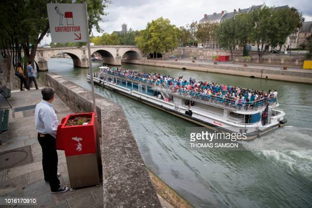 A man stands at a 'uritrottoir' public urinal on August 13 on the SaintLouis island in Paris as a 'bateau mouche' tourist barge cruises past The city...