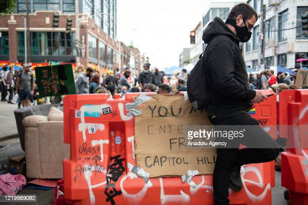 A man stands at an entrance to the âCapitol Hill Organized Protestâ formerly known as the âCapitol Hill Autonomous Zoneâ in Seattle Washington on...