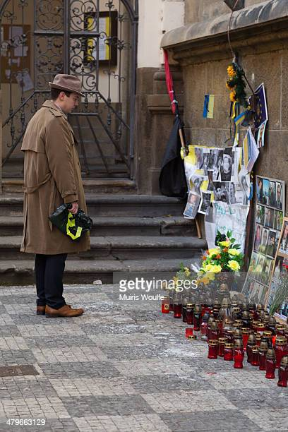 Man stands at an impromptu memorial near Charles Bridge in Prague remembering those in Kiev's Maidan who were killed during a protest that ultimately...