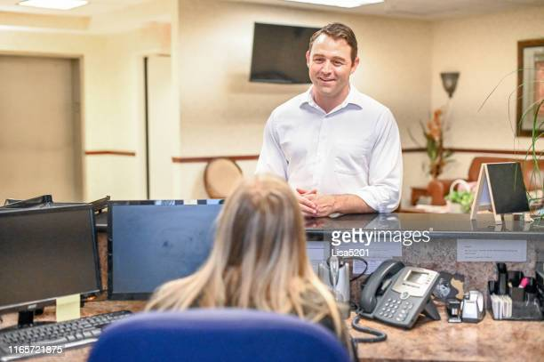 man stands at at reception desk and talks to a receptionist in an office setting - administrative professional day stock pictures, royalty-free photos & images