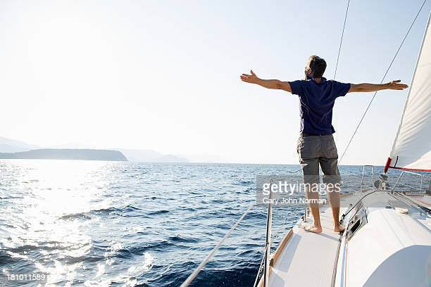 man stands at bow of yacht with arms outstretched