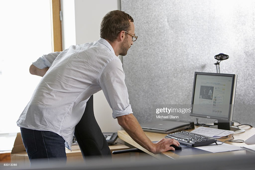 man stands at desk : Stock Photo