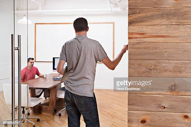 Man stands at door to chat with seated coworker