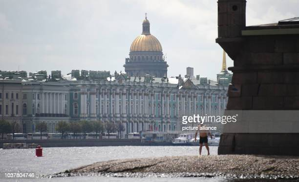A man stands at the banks of river Neva across the Hermitage with the golden cupola of St Isaac's Cathedral in the background in St Petersburg Russia...