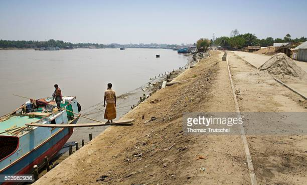 A man stands at the dock of a ship at the port of Khulna next to a newly built Town Protection Embankment which serves to protect the adjacent...