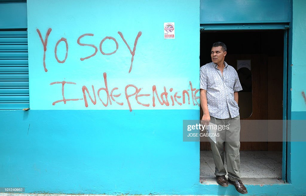 A man stands at the door of his home looking at supporters of ousted Honduran President Manuel Zelaya marching against the military coup, in Tegucigalpa on July 2, 2009. Coup leaders in Honduras vowed that ousted President Manuel Zelaya will 'never return to power' despite mounting international pressure and an ultimatum by the Organization of American States. AFP PHOTO/ Jose CABEZAS