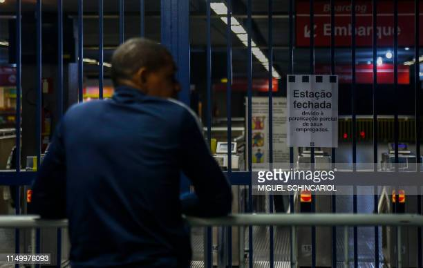 A man stands at the entrance of a closed metro station in Sao Paulo Brazil on June 14 during a national strike called by trade unions over Brazilian...