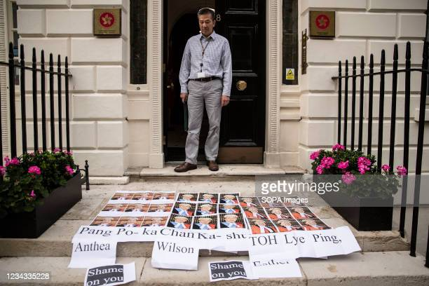 Man stands at the entrance of Hong Kong Economic and Trade Office and looks on at the protesters' display of the self-printed portraits of three...