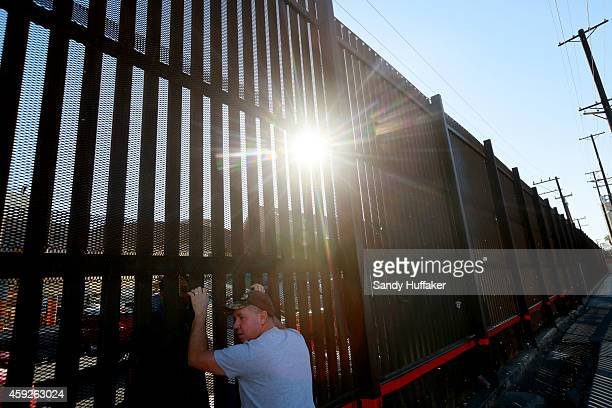 A man stands at the US Mexico border wall on November 19 2014 in Calexico California US President Barack Obama plans to announce executive action on...
