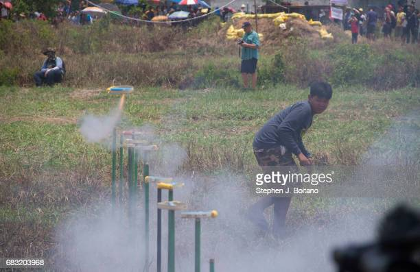 A man stands back as fireworks launch as a gesture to god for the sake of the rainy season during the Ban Bung Fai Rocket Festival in Yasothon...