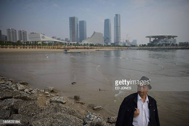 A man stands before the skyline of Xiamen Fujian province on October 25 2013 China's central bank has unveiled a new regime to allow banks to set a...