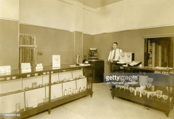 Man stands behind the counter in the sales room for pet food company Canine Kitchens, circa 1933.
