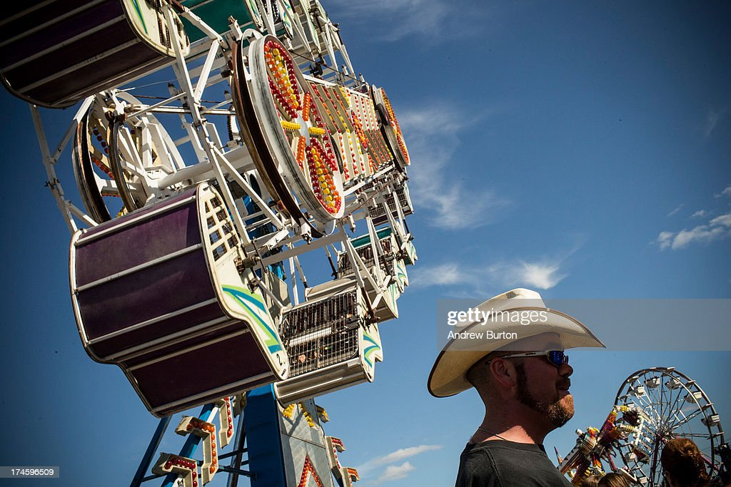 A man stands beneath a ride at the North Dakota state fair on July 27, 2013 in Williston, North Dakota. The western region of North Dakota has seen a rise in crime, automobile accidents and drug usage recently, due in part to the oil boom which has brought tens of thousands of jobs to the region, lowering state unemployment and bringing a surplus to the state budget.