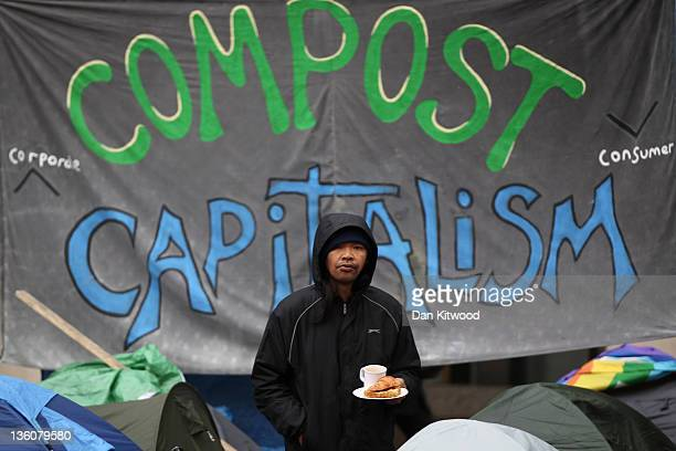 A man stands beneath an anti capitalism poster at the 'Occupy London' camp site outside St Paul's Cathedral on December 19 2011 in London England A...