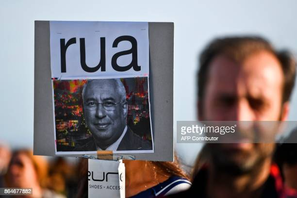 A man stands beside a poster with a portrait of Portuguese Prime Minister Antonio Costa reading 'Out' as hundreds of people gather at the Comercio...