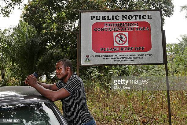 A man stands beside a public notice warning of a contaminated area in Goi Nigeria on Wednesday Jan 13 2016 Twenty years after the oilpollution crisis...