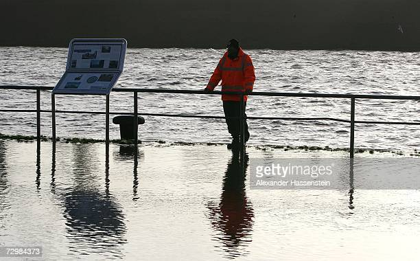 A man stands beside railings and watches as the River Elbe begins to flood the edge of the harbour in the Fischmarkt area of Hamburg on January 12...