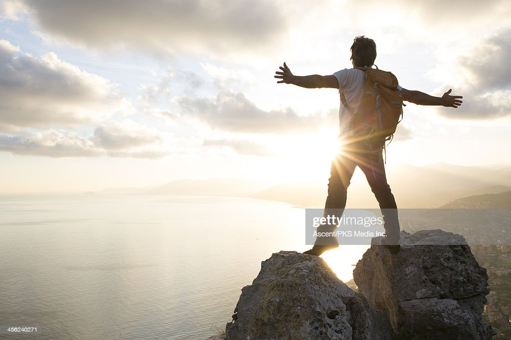 Man stands between boulders on summit, arms out : Stock Photo