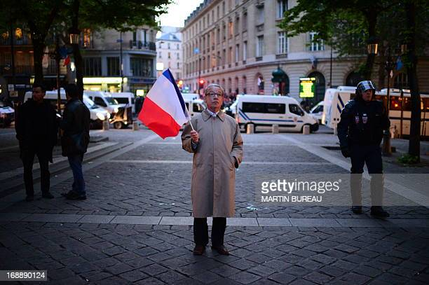 Man stands brandishing a French flag stands during a protest by anti gay-marriage movements on May 16, 2013 outside the Sorbonne University in Paris...