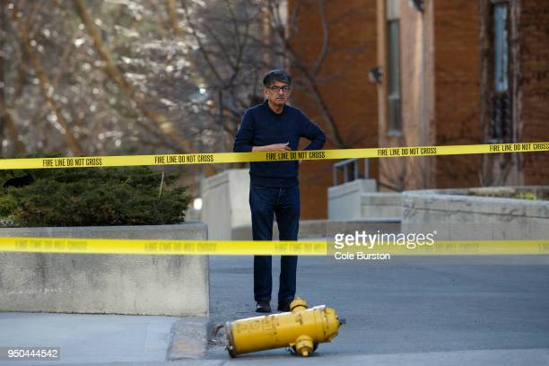 A man stands by a dislodged fire hydrant on Yonge St at near Finch Ave after a van plowed into pedestrians on April 23 2018 in Toronto Canada A...