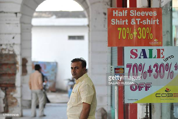 Man stands by a shop window display advertising reduced prices on garments in New Delhi on September 20, 2011. India's benchmark wholesale price...