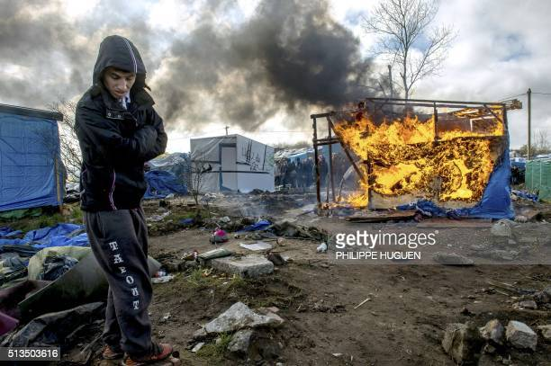 TOPSHOT A man stands by as a makeshift shelter burns in the socalled Jungle migrant camp in the French port city of Calais on March 3 during the...