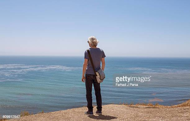Man stands by cliff's edge over the ocean