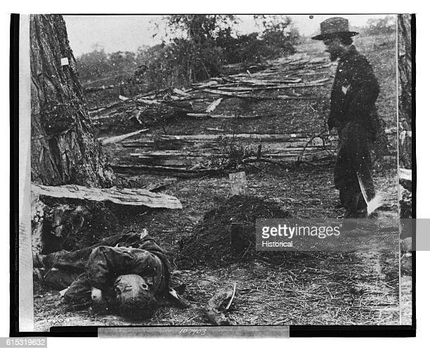 Man stands by the burial mound of a Union soldier. A dead Confederate soldier lies nearby, unburied.