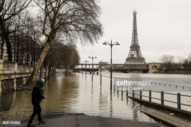 TOPSHOT A man stands by the flooded banks of the river Seine in Paris on January 23 2018 near the Eiffel tower as the Seine level has risen to a...