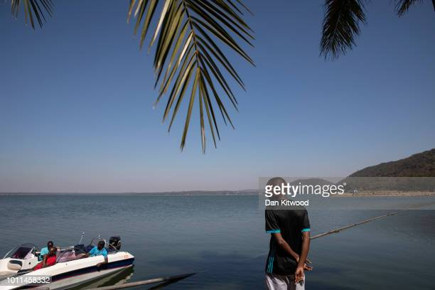 A man stands by the side of Lake Chivero as his friends take a boat ride on August 5 2018 in Harare Zimbabwe Lake Chivero is 32km South West of...