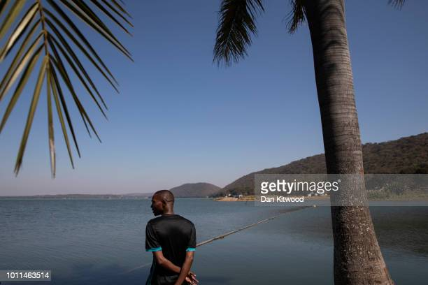A man stands by the side of Lake Chivero on August 5 2018 in Harare Zimbabwe Lake Chivero is 32km South West of Zimbabwe's capital Harare and the...